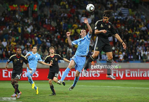 Diego Godin of Uruguay defends an attack by Sami Khedira of Germany during the 2010 FIFA World Cup South Africa Third Place Playoff match between...