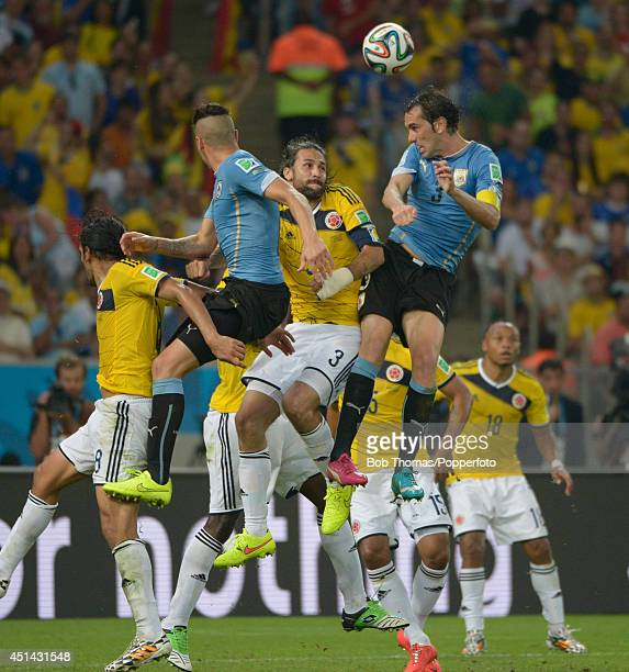 Diego Godin of Uruguay heads the ball with Mario Yepes of Colombia during the 2014 FIFA World Cup Brazil round of 16 match between Colombia and...