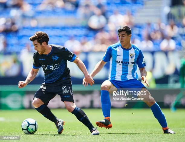 Diego Gonzalez of Malaga competes for the ball with Ibai Gomez of Deportivo Alaves during the La Liga match between Malaga and Deportivo Alaves at...