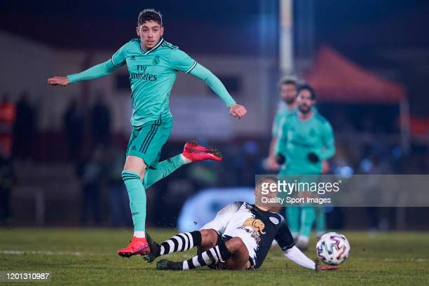 Diego Gonzalez of Unionistas CF competes for the ball with Federico Valverde of Real Madrid CF during the Copa del Rey round of 32 match between...