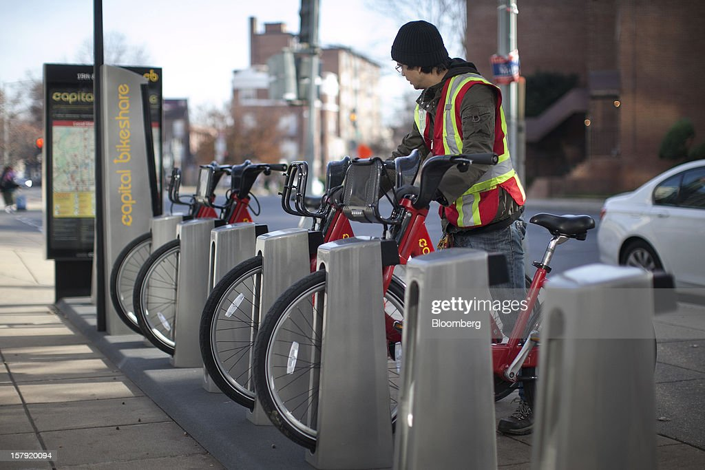 Diego Jaramillo adds a Capital Bikeshare bicycle to a docking station in Washington, D.C., U.S., on Friday, Dec. 7, 2012. Since September 2010, Capital Bikeshare has dispersed more than 1700 bikes for rent across the city and has totaled over 3.5 million rides since Sept. 2011. Alta Bicycle Share, the company that was awarded the contract to run the program, has installed 191 solar-powered docking stations throughout the District and Arlington, Virginia. Photographer: Andrew Harrer/Bloomberg via Getty Images