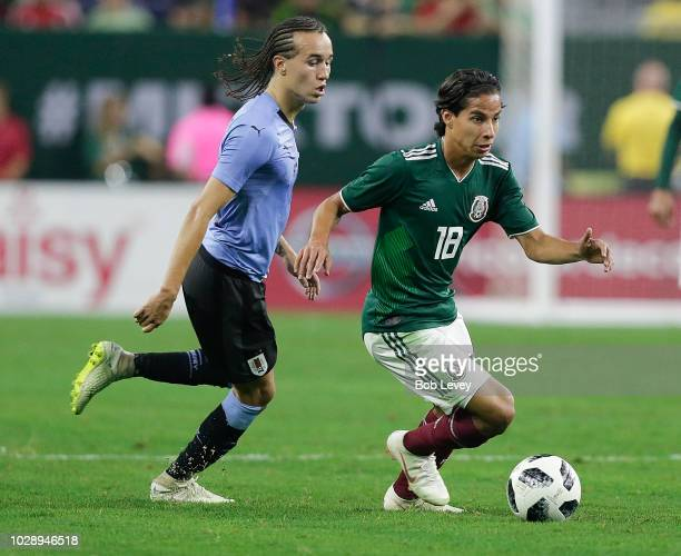 Diego Lainez of Mexico dribbles past Diego Laxalt of Uruguay in the second half during the International Friendly match between Mexico and Uruguay at...