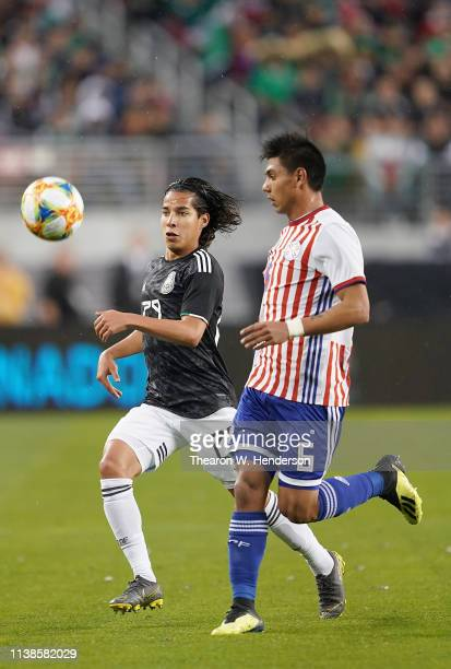 Diego Lainez of the Mexico National team chases after control of the ball with Santiago Arzamendia of Paraguay during the first half of their soccer...