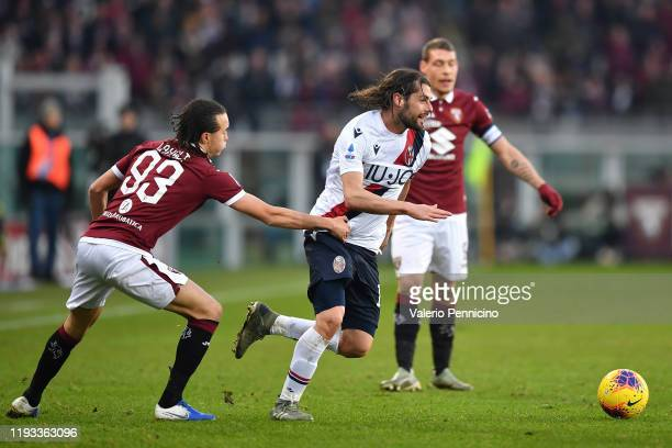 Diego Laxalt of Torino FC competes with Andrea Poli of Bologna FC during the Serie A match between Torino FC and Bologna FC at Stadio Olimpico di...