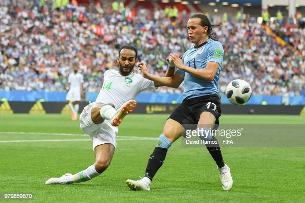 Diego Laxalt of Uruguay competes for the ball with Abdullah Otayf of Saudi Arabia during the 2018 FIFA World Cup Russia group A match between Uruguay...