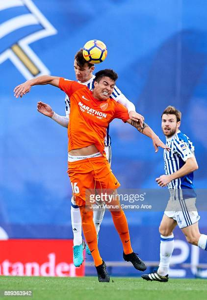 Diego Llorente of Real Sociedad duels for the ball with Adalberto Penaranda of Malaga CF during the La Liga match between Real Sociedad de Futbol and...
