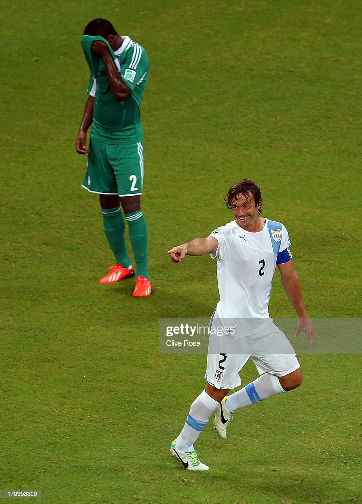 Diego Lugano of Uruguay celebrates scoring his team's first goal as Godfrey Oboabona of Nigeria looks dejected during the FIFA Confederations Cup Brazil 2013 Group B match between Nigeria and Uruguay at Estadio Octavio Mangabeira (Arena Fonte Nova Salvador) on June 20, 2013 in Salvador, Brazil.