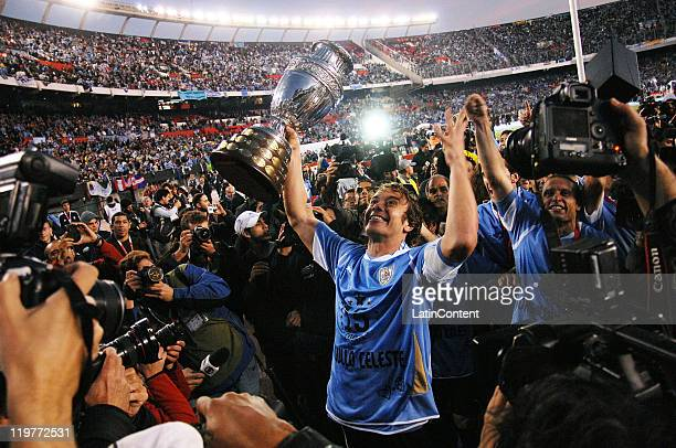 Diego Lugano of Uruguay raises the trophy celebrating with teammates the victory of the Copa America 2011 against Paraguay at Antonio Vespucio...