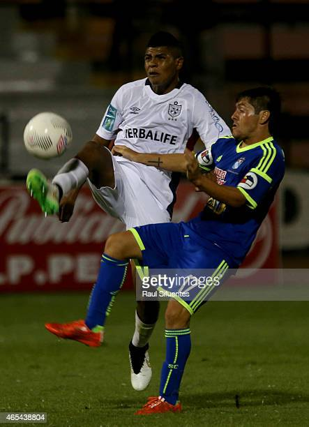 Diego Manicero of Sporting Cristal struggles for the ball with Wilder Cartagena of San Martin during a match between San Martin and Sporting Cristal...