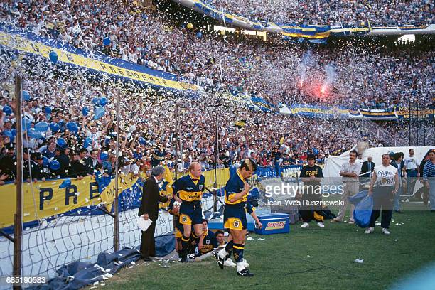 Diego Maradona enters the field for an Argentina soccer championship match against San Lorenzo as fans toss confetti from the stands.