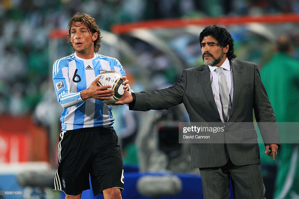 Diego Maradona head coach of Argentina hands the ball to Gabriel Heinze of Argentina during the 2010 FIFA World Cup South Africa Group B match between Argentina and Nigeria at Ellis Park Stadium on June 12, 2010 in Johannesburg, South Africa.