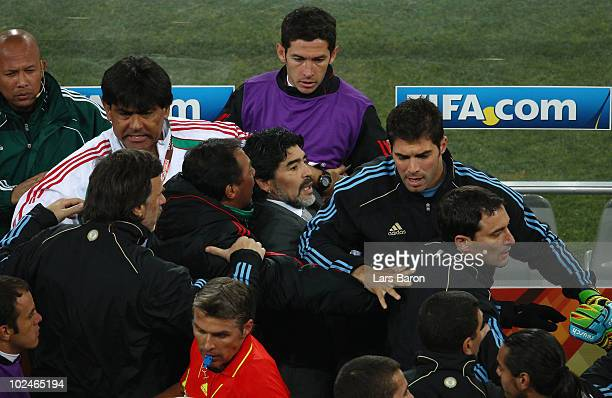 Diego Maradona head coach of Argentina is restrained during a scuffle between the two teams as half time is called during the 2010 FIFA World Cup...