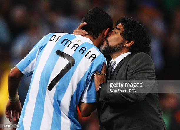 Diego Maradona head coach of Argentina thanks his player Angel Di Maria with a kiss after being substituted during the 2010 FIFA World Cup South...