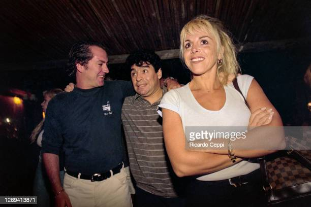 Diego Maradona hugs a fan as he arrives in a limousine with his wife Claudia Villafañe to a party at Conrad Hotel on January 08, 1999 in Punta del...