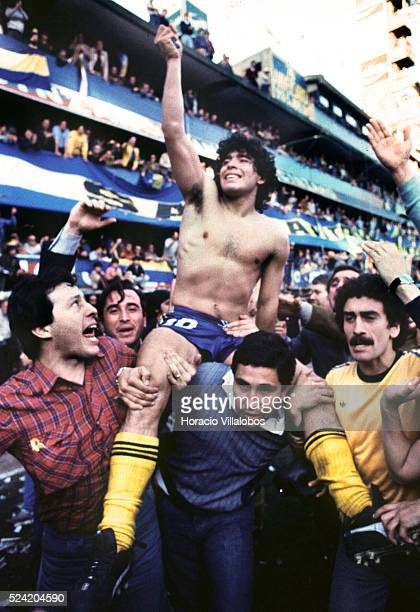 Diego Maradona is carried in triumph by Boca Juniors fans after his team won an Argentine soccer championship in August 1981