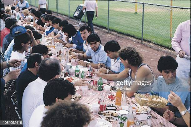Diego Maradona of Argentina eats a barbecue with his teammates ahead of the 1986 FIFA World Cup at Club America training camp on May, 1986 in Mexico...