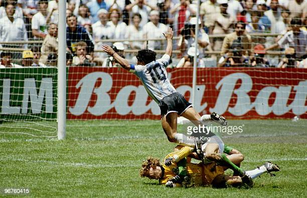 Diego Maradona of Argentina goes flying over the challenges of West German goalkeeper Harald Schumacher and defender Karl Heinz Foerster during the...
