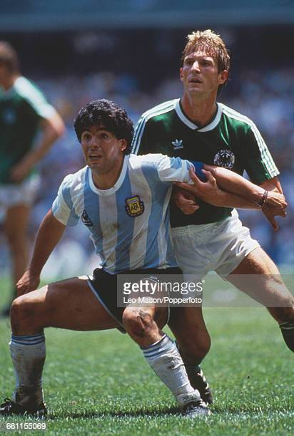 Diego Maradona of Argentina holds back KarlHeinz Foerster of West Germany in the 1986 FIFA World Cup final game between Argentina and West Germany at...