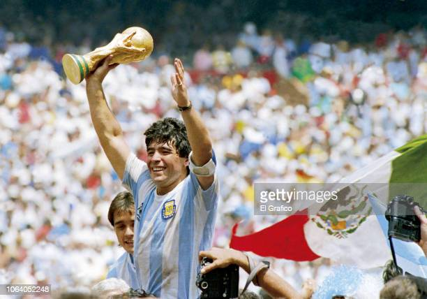 Diego Maradona of Argentina holds the World Cup trophy after defeating West Germany 3-2 during the 1986 FIFA World Cup Final match at the Azteca...