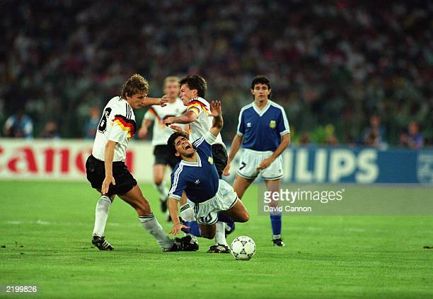 Diego Maradona of Argentina is brought down by both Guido Buchwald and Lothar Matthaus of West Germany during the FIFA World Cup Finals 1990 Final...