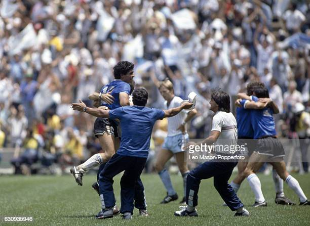 Diego Maradona of Argentina is congratulated by teammates after scoring one of his two goals during the World Cup QuarterFinal match between England...