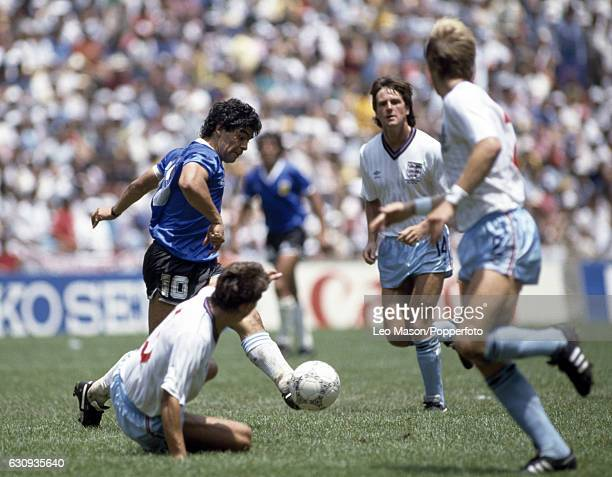 Diego Maradona of Argentina is surrounded by England players left to right Kenny Sansom Terry Fenwick and Gary Stevens during the World Cup...