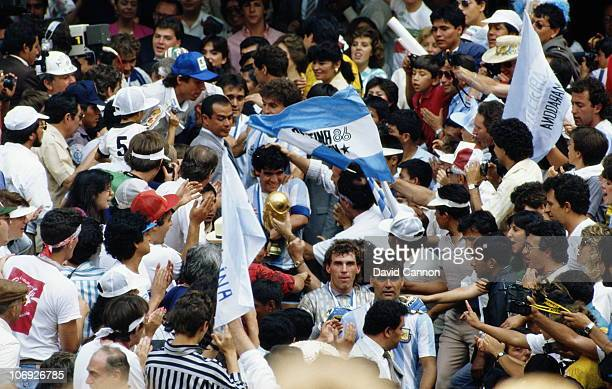 Diego Maradona of Argentina is surrounded by fans as he carries the trophy after winning the 1986 FIFA World Cup Final against West Germany on 29th...