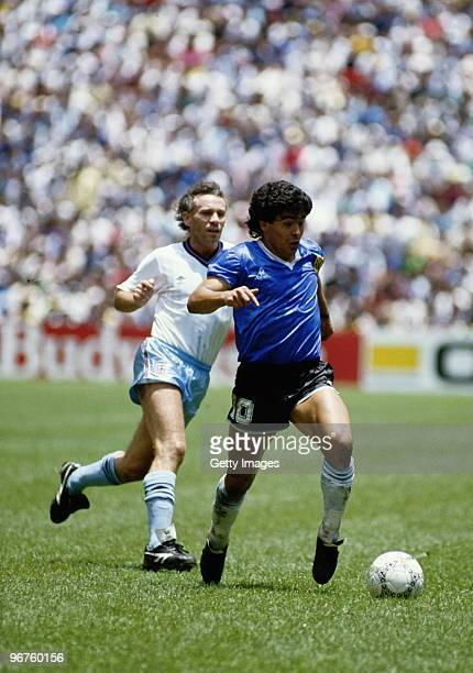 Diego Maradona of Argentina runs with the ball passed Peter Reid of England during the 1986 FIFA World Cup Quarter Final on 22 June 1986 at the...