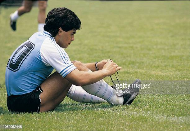 Diego Maradona of Argentina ties his shoe string during a training session as part of the 1986 FIFA World Cup at Club America training camp on June,...