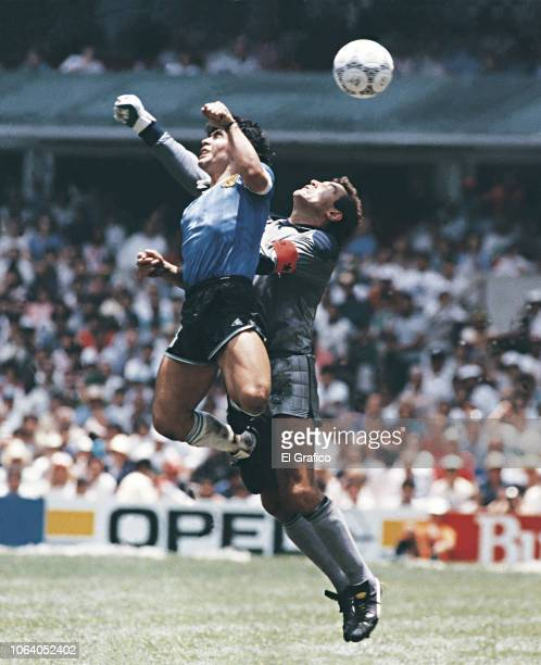 Diego Maradona of Argentina uses his hand to score the first goal of his team during a 1986 FIFA World Cup Quarter Final match between Argentina and...