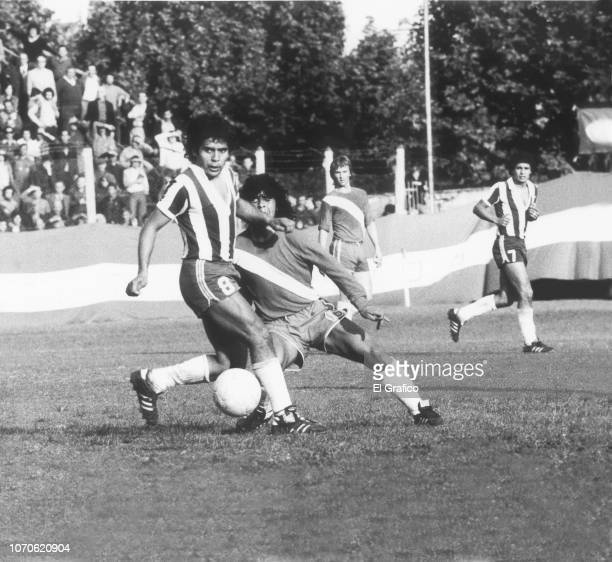 Diego Maradona of Argentinos fights for the ball with Juan Domingo Cabrera of Talleres during a match between Argentinos Juniors and Talleres as part...