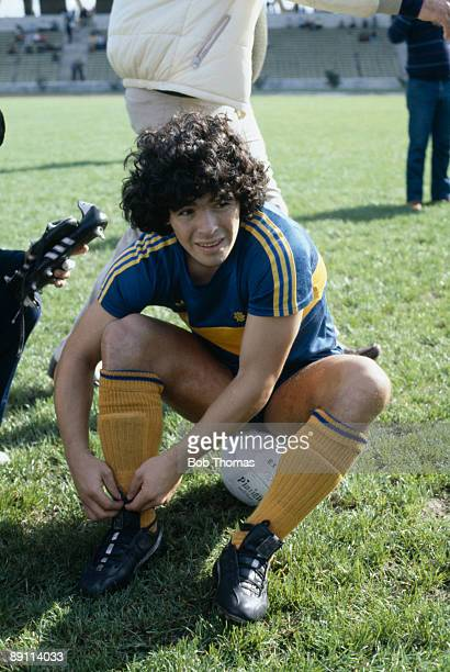 Diego Maradona of Boca Juniors sits on a ball while tying up his boot laces before the match between Boca Juniors and Talleres in Buenos Aires...