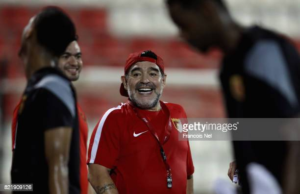 Diego Maradona the new head coach of Fujairah FC share a joke with players during a training session at Fujairah Stadium on July 24 2017 in Fujairah...