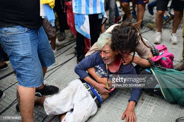 Diego Maradona's fan cries after being injured during scuffles with the police while waiting to enter the Government House to pay tribute to late...