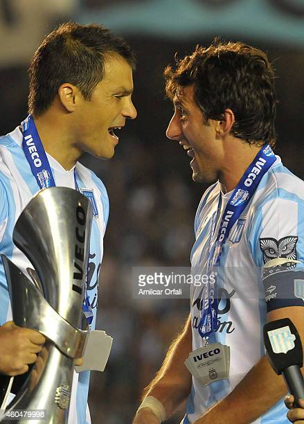 Diego Milito and Sebastian Saja of Racing Club celebrate the championship holding the trophy after winning a match between Racing Club and Godoy Cruz...