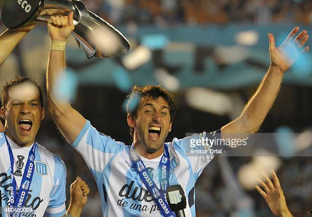 Diego Milito of Racing Club hold the trophy as he celebrates the championship after winning a match between Racing Club and Godoy Cruz as part of...