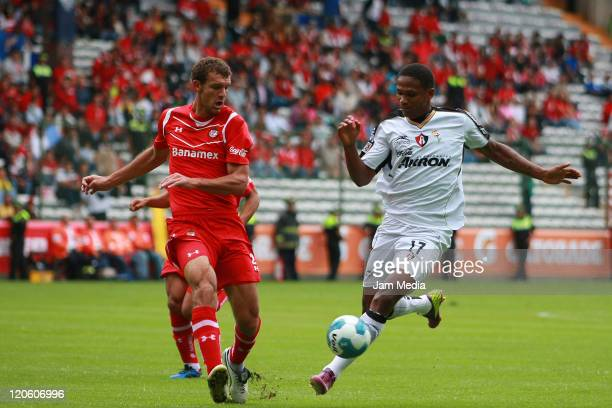 Diego Novaretti of Toluca struggles for the ball with Georhie Welcome of Atlas during a match as part of the Apertura 2011 at Nemesio Diez Stadium on...