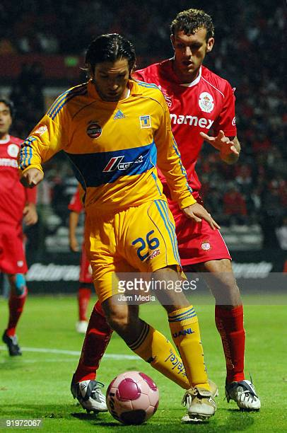 Diego Novaretti of Toluca vies for the ball with Francisco Fonseca of Tigres during their match as part of the Mexican Football League at Nemesio...