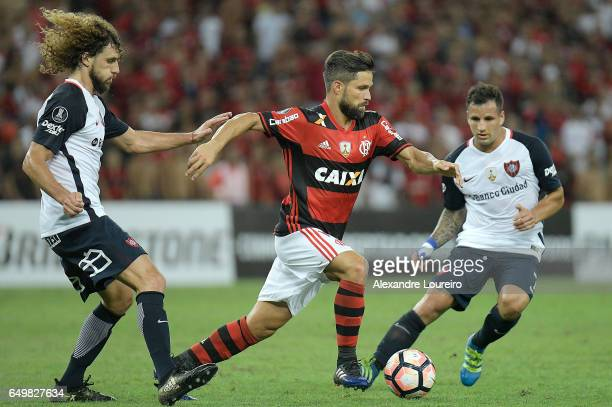 Diego of Flamengo battles for the ball with Fabricio Coloccini and Franco Mussis of San Lorenzo during the match between Flamengo and San Lorenzo as...