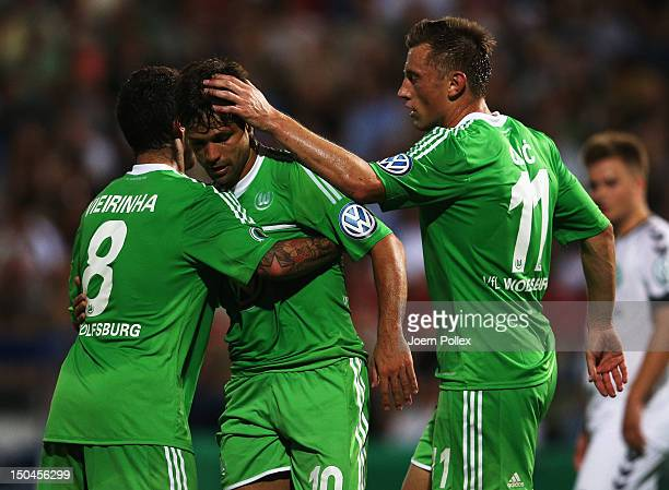 Diego of Wolfsburg celebrates with his team mates after scoring his team's third goal during the DFB Cup first round match between SV FC Schoenberg...