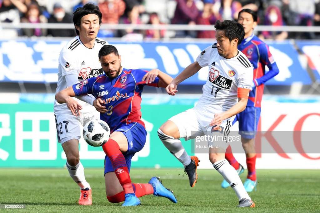 Diego Oliveira (C) of FC Tokyo competes for the ball against Kazuki Oiwa (L) and Shingo Tomita (R) of Vegalta Sendai during the J.League J1 match between FC Tokyo and Vegalta Sendai at Ajinomoto Stadium on March 3, 2018 in Chofu, Tokyo, Japan.