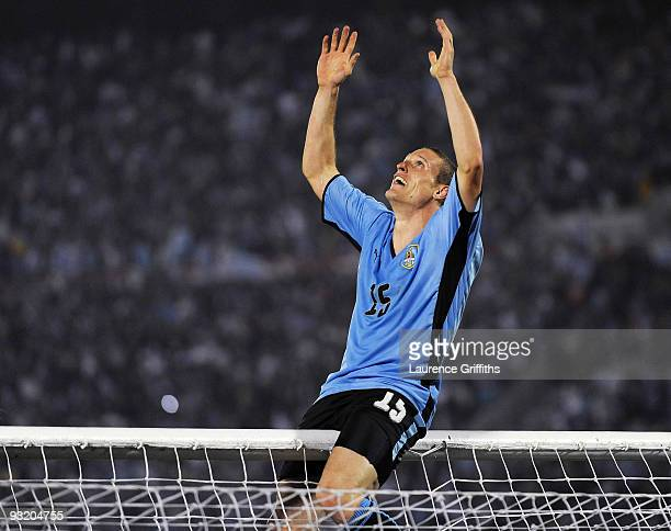 Diego Perez of Uruguay celebrates by climbing onto the crossbar after the 2010 FIFA World Cup Play Off Second Leg Match between Uruguay and Costa...