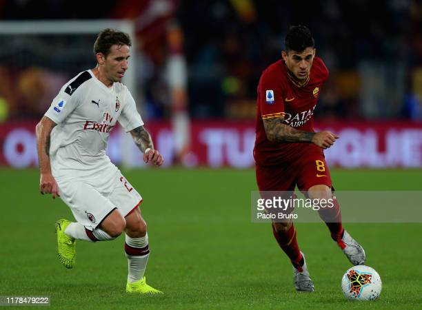 Diego Perotti of AS Roma competes for the ball with Lucas Biglia of AC Milan during the Serie A match between AS Roma and AC Milan at Stadio Olimpico...