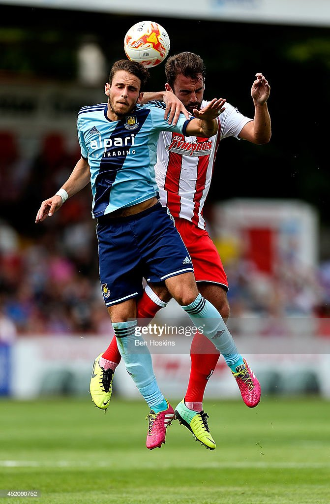 Diego Poyet of West Ham and Simon Walton of Stevenage challenge for an aerial ball during the Pre Season Friendly match between Stevenage and West Ham United at The Lamex Stadium on July 12, 2014 in Stevenage, England.