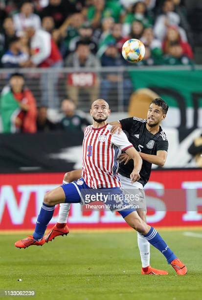 Diego Reyes of the Mexico National team battles for control of the ball with Carlos Gonzalez of Paraguay during the first half of their soccer game...