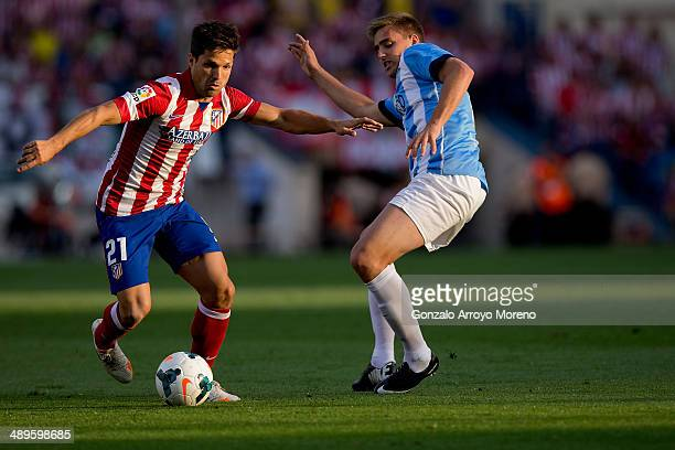Diego Ribas of Atletico de Madrid competes for the ball with Juan Miguel Jimenez alias Juanmi of Malaga CF during the La Liga match between Club...