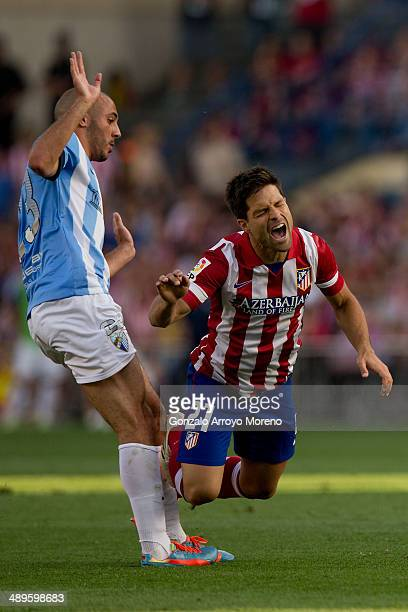 Diego Ribas of Atletico de Madrid grimaces in pain after being tackled by Amrabat of Malaga CF during the La Liga match between Club Atletico de...