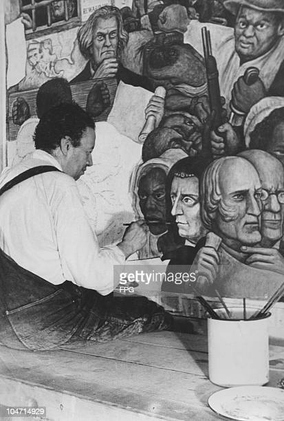 Diego Rivera Mexican artist sits finishing a painting circa 1930