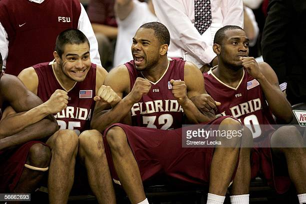 Diego Romero and teammates Alexander Johnson and Ralph Mims of the Florida State Seminoles celebrate on the bench against the Wake Forest Demon...