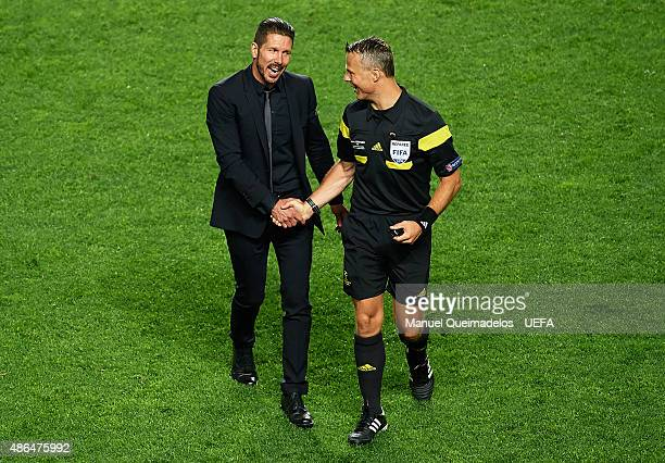 Diego Simeone coach of Club Atletico de Madrid shakes hands with referee Bjorn Kuipers during the UEFA Champions League Final between Real Madrid CF...